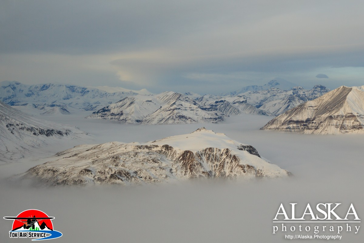 Inside Wrangell-Saint Elias National Park, Gold Hill rises above the fog, with Mount Sanford in the distance and Mount Jarvis on the left.