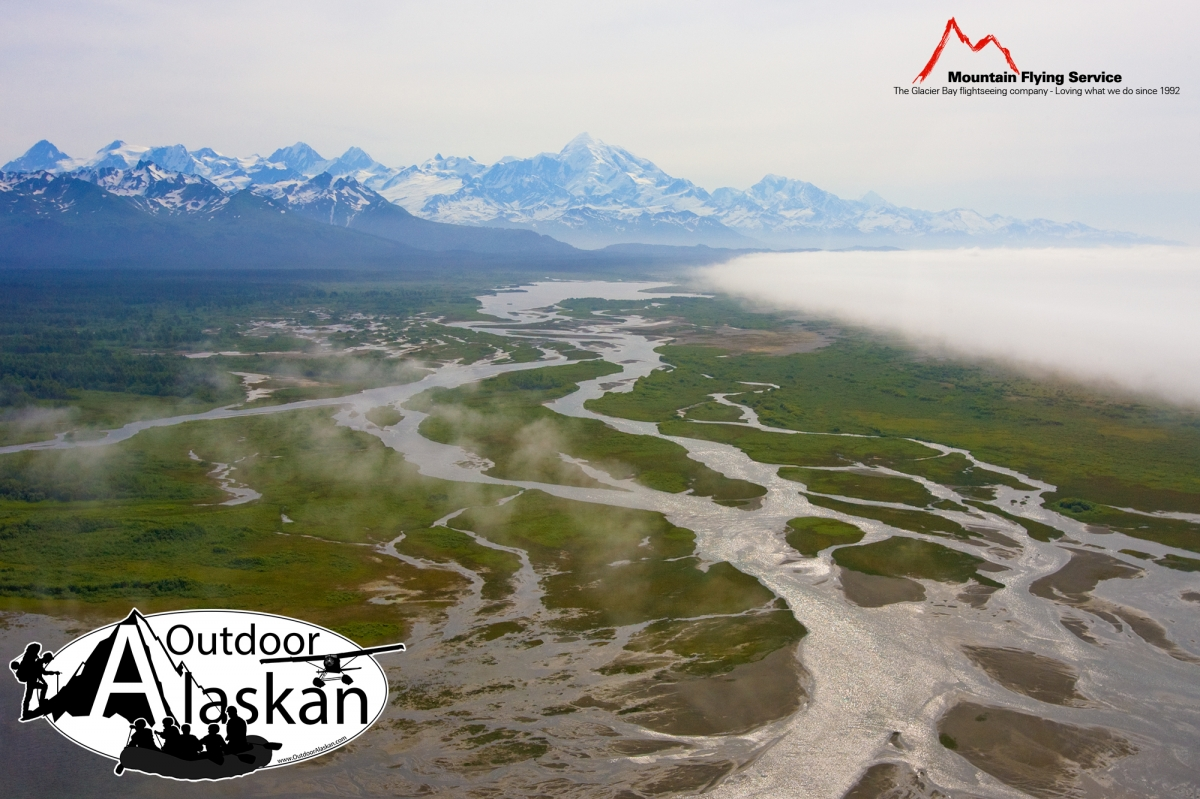 A massive fog bank moves in from the Gulf of Alaska towards the East Alsek and Doame Rivers. Whilest Mount Fairweather looms above the other mountains of the Fairweather Range.