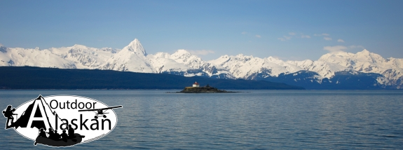 In the middle of Lynn Canal, Eldred Rock and lighthouse sit in the foreground with Sullivan Island and the Chilkat Range in the background.