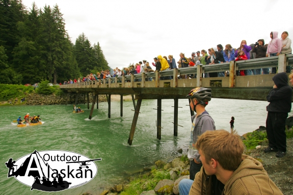 Spectators watch as rafts compete in the Mad Raft Race. An annual 4th of July tradition in Haines, where rafters float from Chilkoot Lake to the bridge that crosses the Chilkoot River.