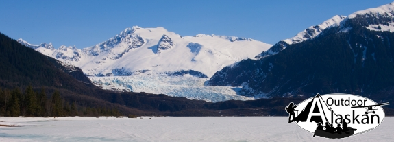 Mendehall Glacier flows into a frozen Mendehall Lake. Mount Wrather in the center and Mendehall Tower rise above the left ridge.
