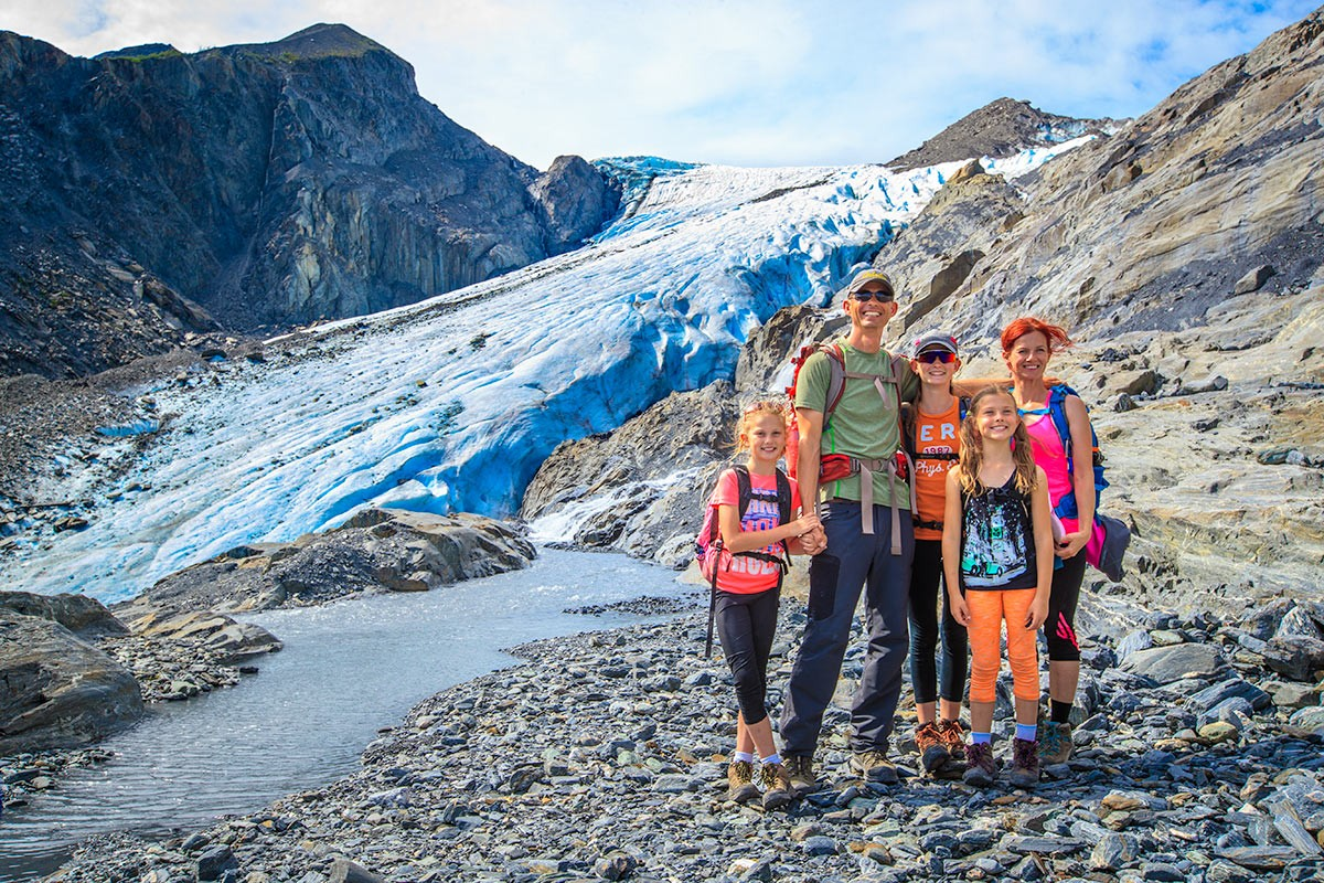 A family stands out in front of Worthington Glacier on the hike out to it.