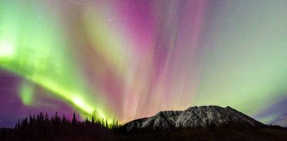 The sky fills with color while chasing the aurora borealis in the Yukon.