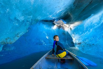 A boy canoes under an old drainage tunnel of Valdez Glacier.