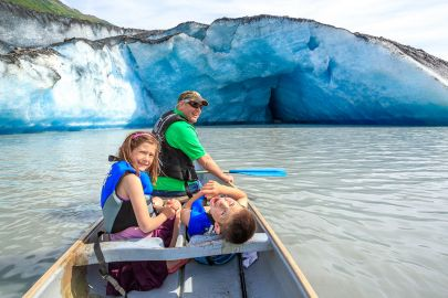 A grandpa and his grandkids smile while paddling out to a giant iceberg of Valdez Glacier.