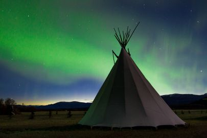 The northern lights dance as the sun rises behind a teepee in the Yukon.